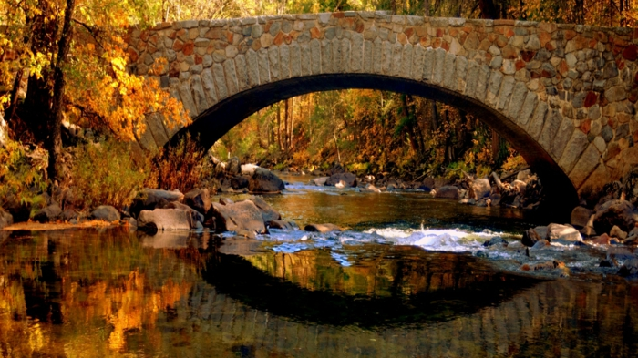 imagenes de otoño, puente de piedras con el agua del rio lleno de piedras y arboles de otoño alrededor