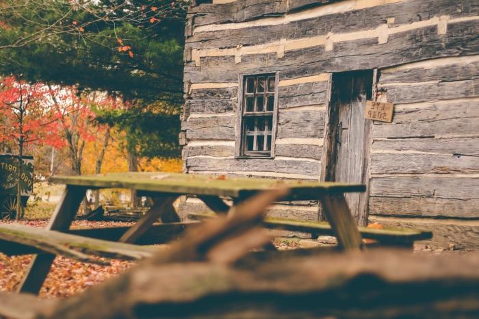 imagenes otoñales, casa de madera con banco con mesa de madera y el suelo lleno de hojas de colores