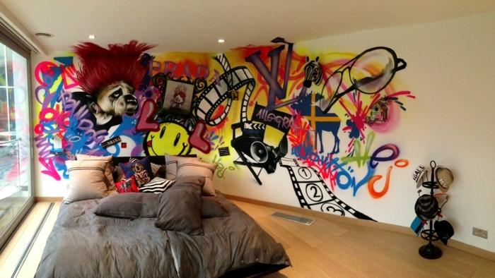 literas juveniles, pared congraffiti, cama con muchos cojines. habitación de chico con estantería para gorras