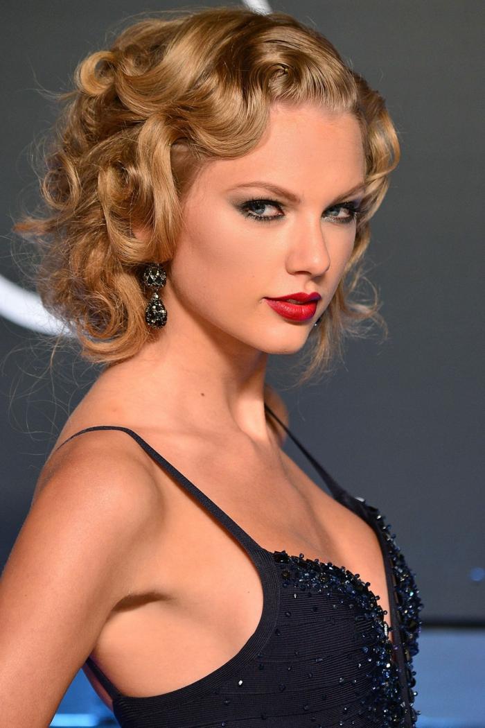 ondas al agua pelo corto, Taylor Swift con media melena rubia rizada con labial rojo fuerte y vestido negro