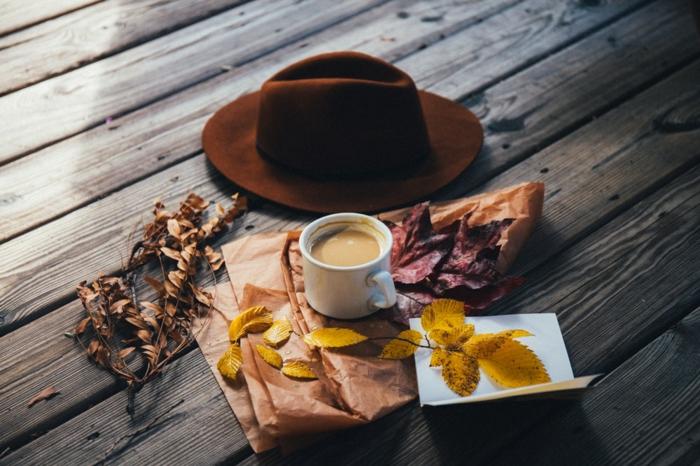 paisajes de ensueño, en la superficie de madera un sombrero marron con taza blanca con cafe dentro