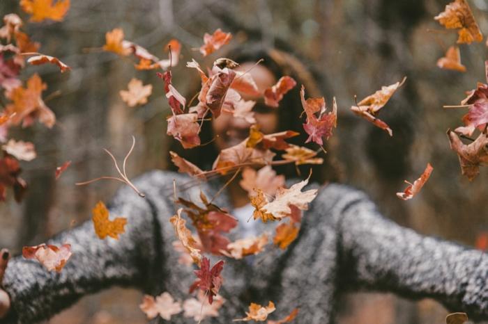 paisajes preciosos, mujer tirando las hojas secas de otoño al aire, feliz de estar de paseo por el bosque