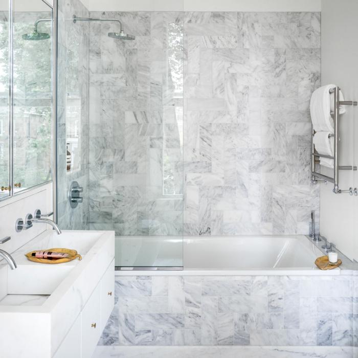 parquet ceramico, bañera decorada con mármol de colores blanco y gris, con espejos en los armarios del baño