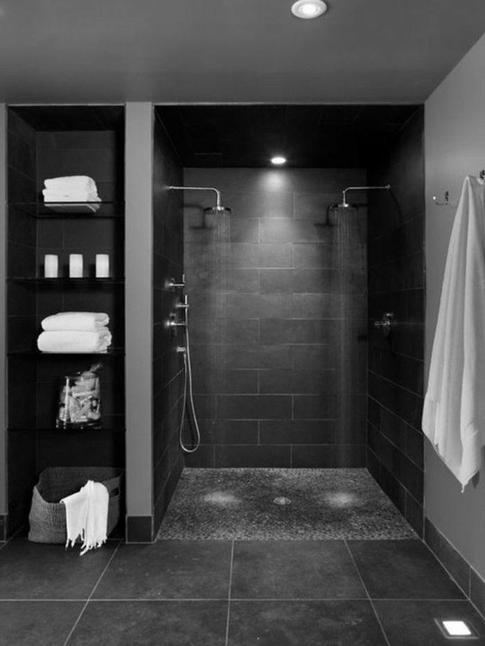 baño decorado en gris oscuro con pequeña cabina de ducha y baldosas grandes, estantería moderna