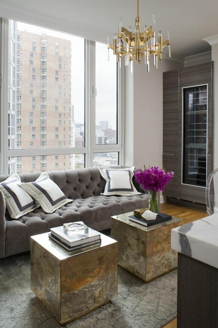 pisos decorados, sofá grande en gris claro con otomanas metálicas con jarrón con flores lilas