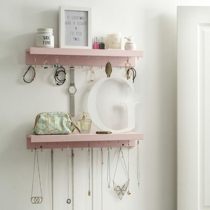 pisos modernos, estantería en color rosa claro con ganchos para pendientes, marco para fotos