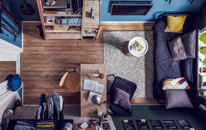 pisos modernos, sofá de color azul oscuro enfrente de la ventana. alfombra gris rectangular en el suelo