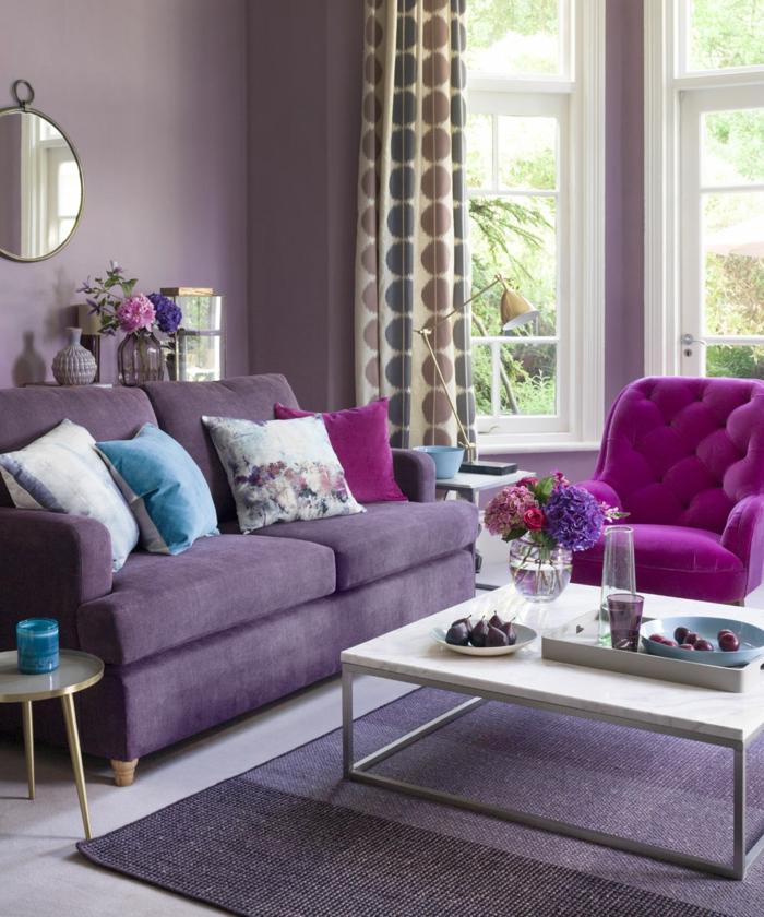 pisos modernos, sofás en color morado y en color lila, paredes en lila con espejo redondo