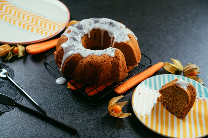 bizcocho casero adornado con glaseado real y semillas de chia, mesa negra adornada con platos en blanco y naranja
