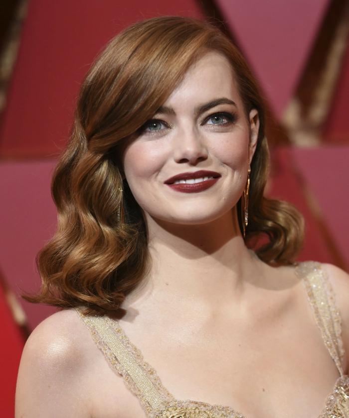 recogidos con ondas Emma Stone con media melena de color cobre con ondulaciones y labial rojo fuerte