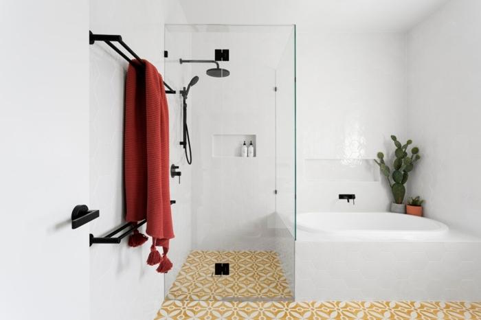 suelos ceramicos, suelo de color amarillo con detalles blancos, toalla roja, bañera blanca con azulejos
