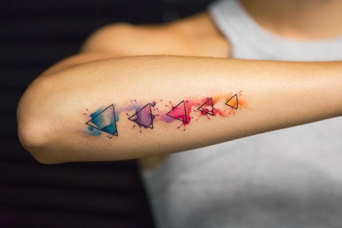 tatuajes geométricos simbolicos con pintura acuarela, tatuaje en el antebrazo con triángulos