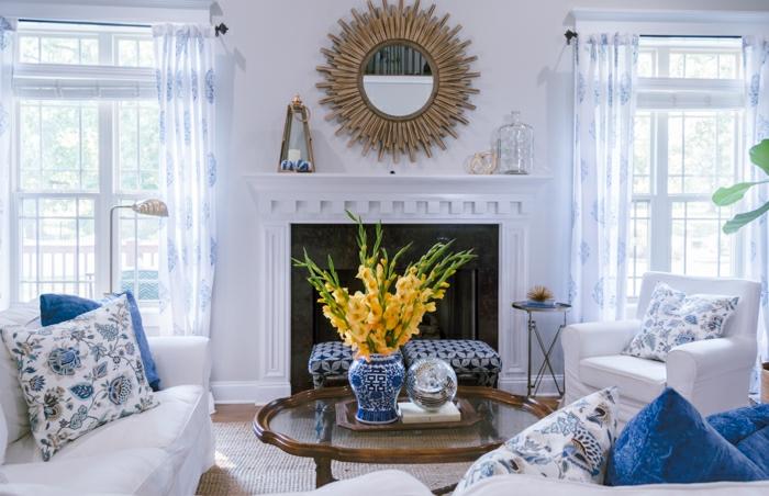 salón moderno decorado con mucho encanto, decoración en blanco y azul, espejo vintaje sol, ideas sobre cómo decorar una chimenea de leña