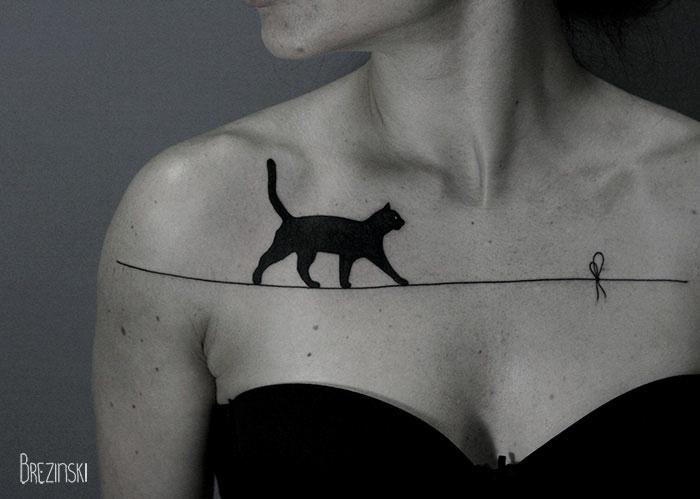diseños de tatuajes surrealistas, gato caminando por una cuerda, tatuaje en el pecho, ideas originales de tatuajes