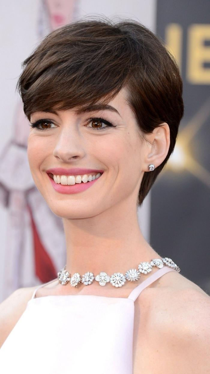 cortes de pelo modernos cortos, Anne Hathaway con corte de pelo pixie con flequillo a un lado, ideas cara oval