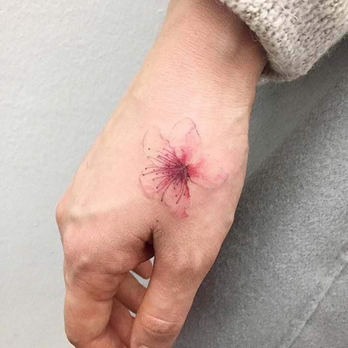 tatuajes pequeños hombre y mujer, preciosa flor tatuada en la mano, diseños de tatuajes femeninos