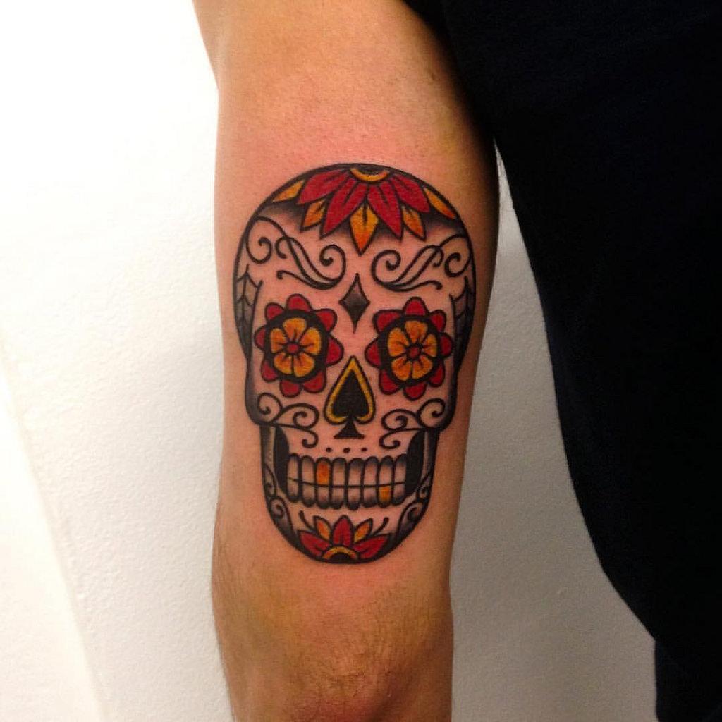 tatuajes para hombres en el brazo propuestas clásicas, calacera tatuada en el brazo en colores intensos, ejemplos de tatuajes old school calaveras