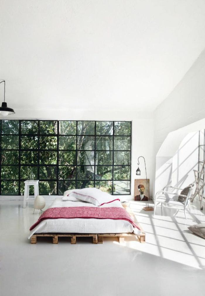 grande dormitorio decorado en blanco con techo alto y cama de palets, grandes ventanales decoración original