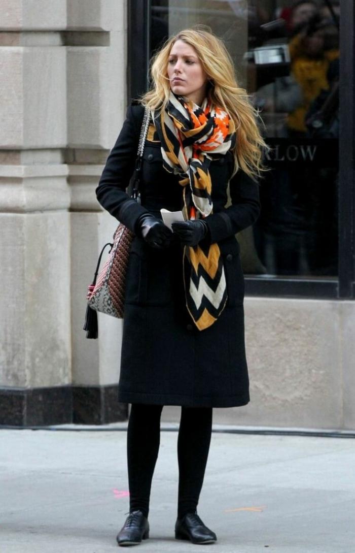 Blake Lively con un abrigo negro adornado de una bufanda con elementos geométricos en colores cálidos