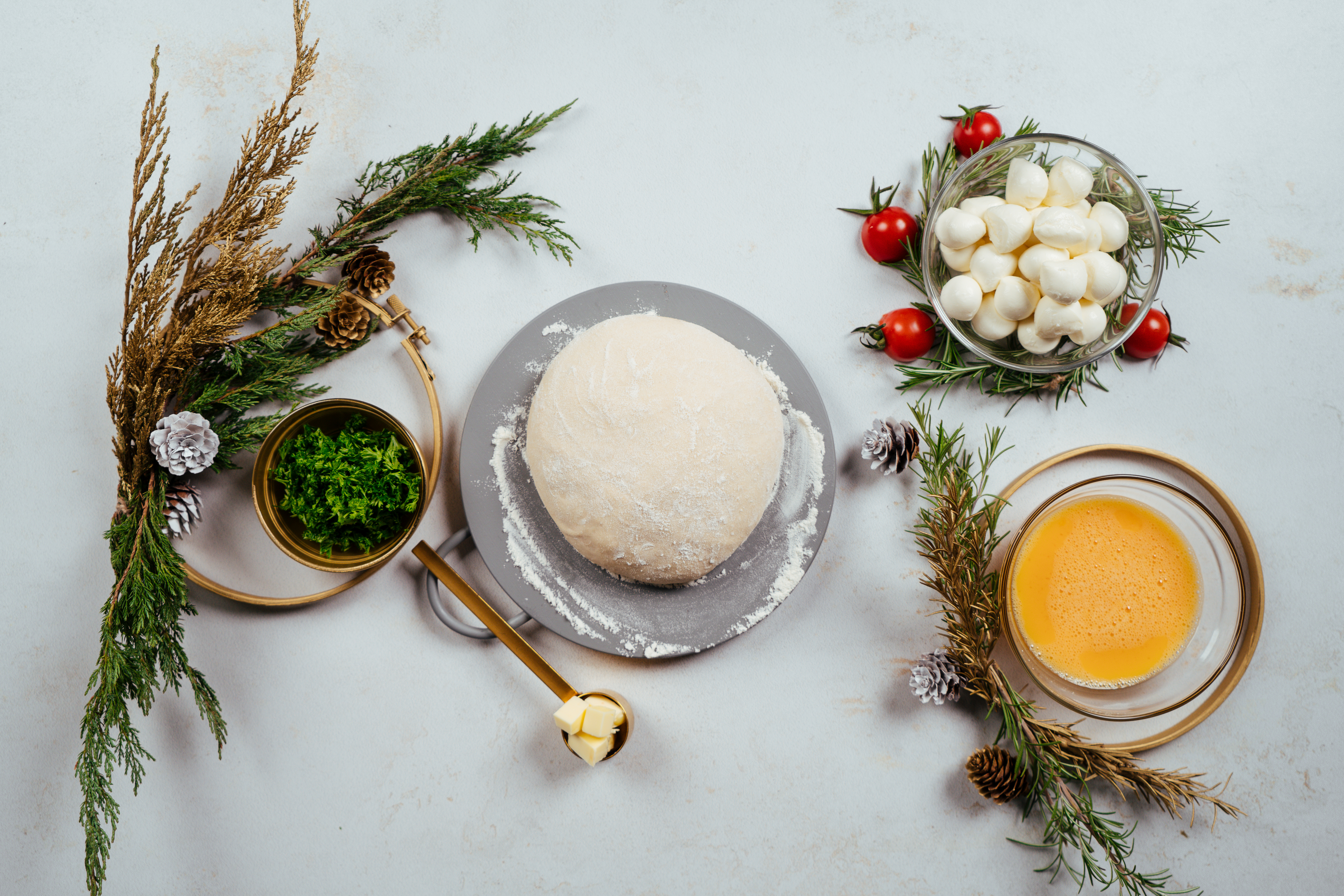 ingredientes para hacer pan de navidad, cilantro picado, masa para pizza, bolas de mozzarella, yemas de huevo batidas