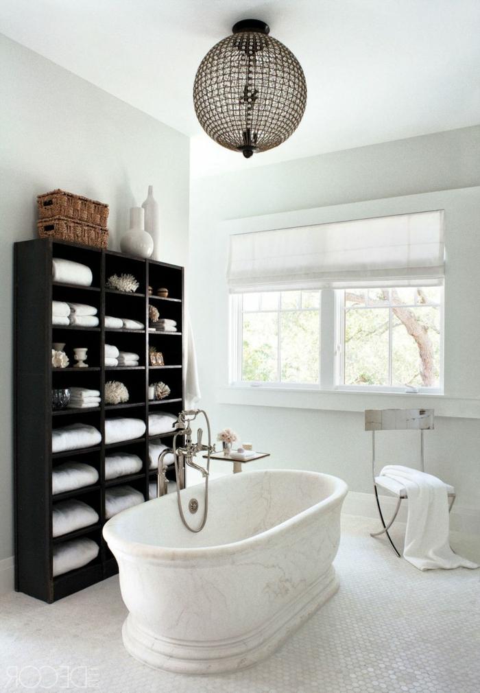 cuarto de baño decorado en colores claros con bañera vintage de mármol, armario de madera