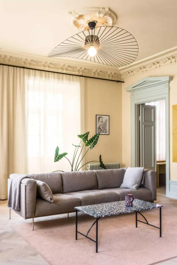 salón moderno decorado en tonos pastel, paredes con color arena pared, lámpara de diseño, sofa en gris