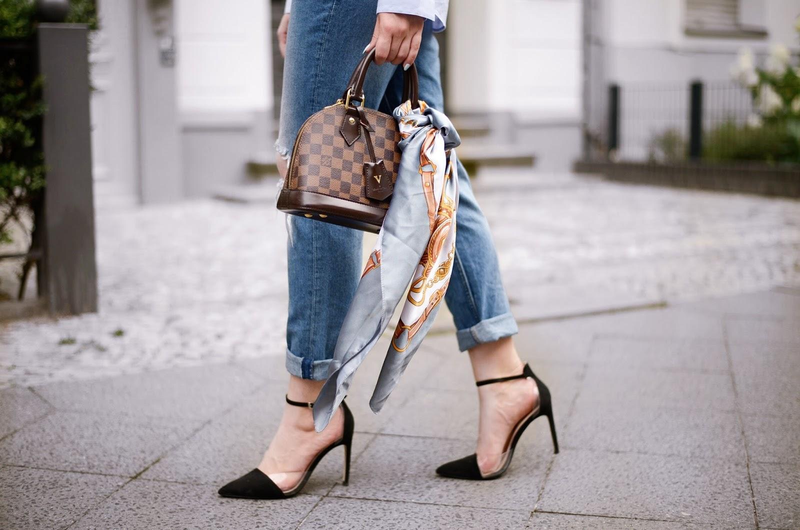 como ponerse un pañuelo en el bolso, outfit moderno y elegante, tacones altos negros, vaqueros, pañuelo de seda