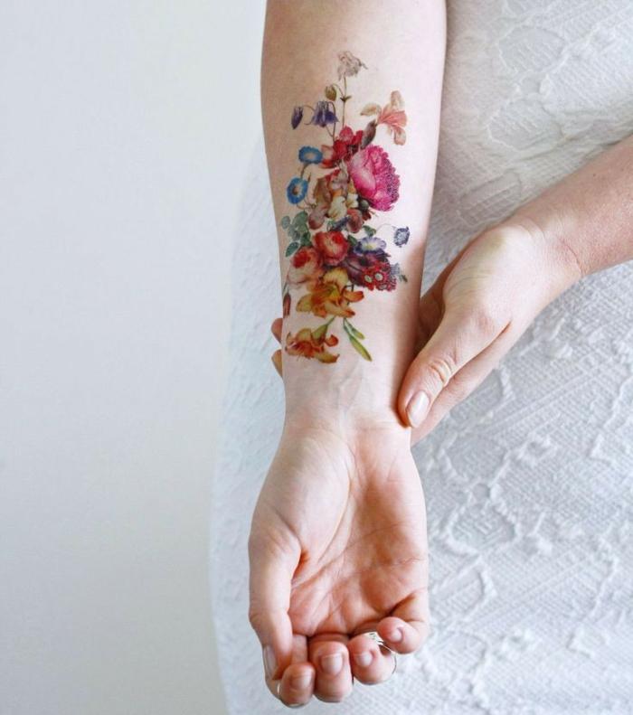 tatuajes tradicionales inspriados en la cultura vintage, antebrazo mujer tatuado con bonitas flores colores intensos