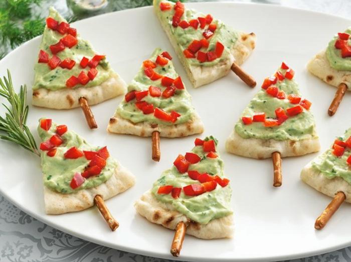 propuestas de aperitivos sencillos y originales para hacer en Navidad, mini pizzas con salsa de aguacate y pimientos rojos