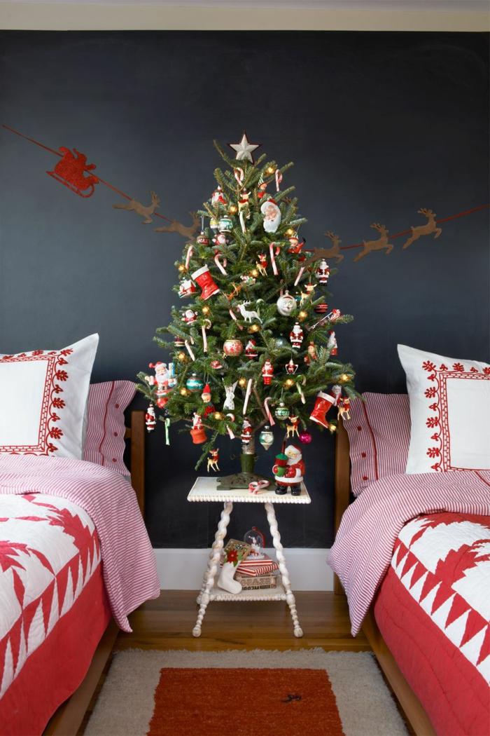 arboles navideños decorados de manera tradicional, dormitorio con dos camas, pequeño árbol navideño con adornos en rojo