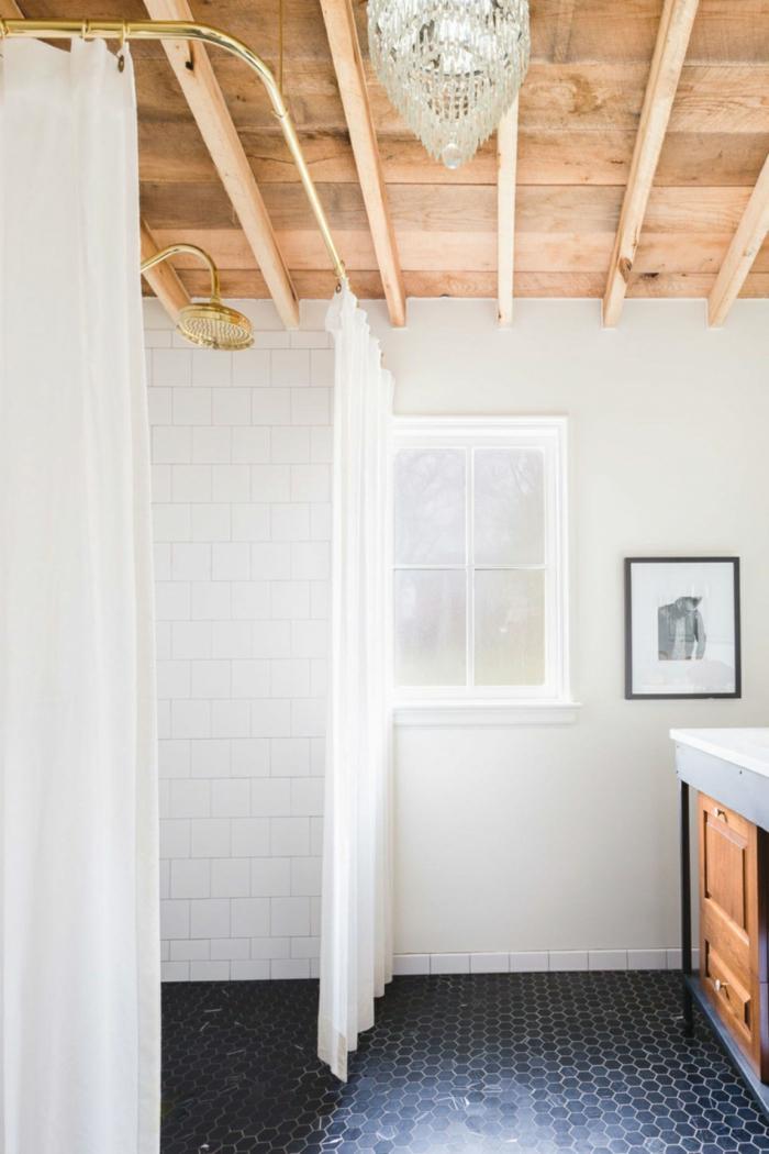 baño decorado en blanco y negro con techo con vigas, paredes en blanco y azulejos negros de forma hexagonal
