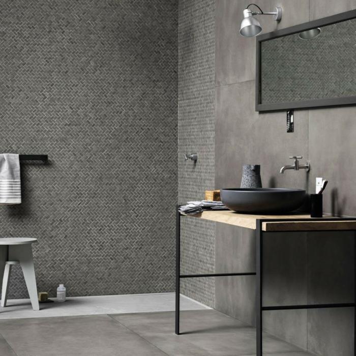 baños grises decorados en estilo industrial, paredes con azulejos de diseño, espejo moderno, asuelo con baldosas grises