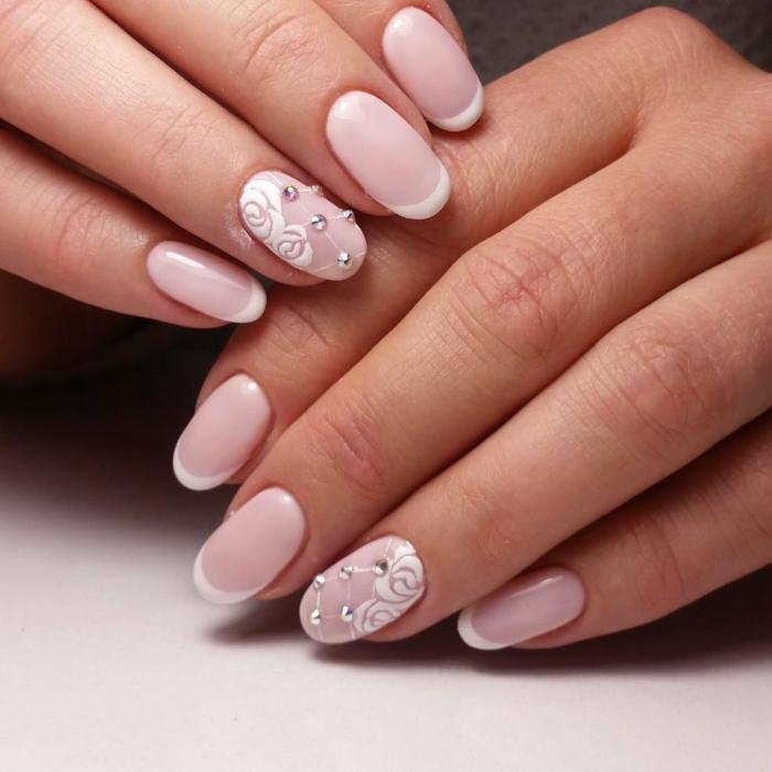 diseño delicado y elegante de uñas de acrilico pintadas en rosado claro, uñas francesas con elementos decorativos, motivos florales