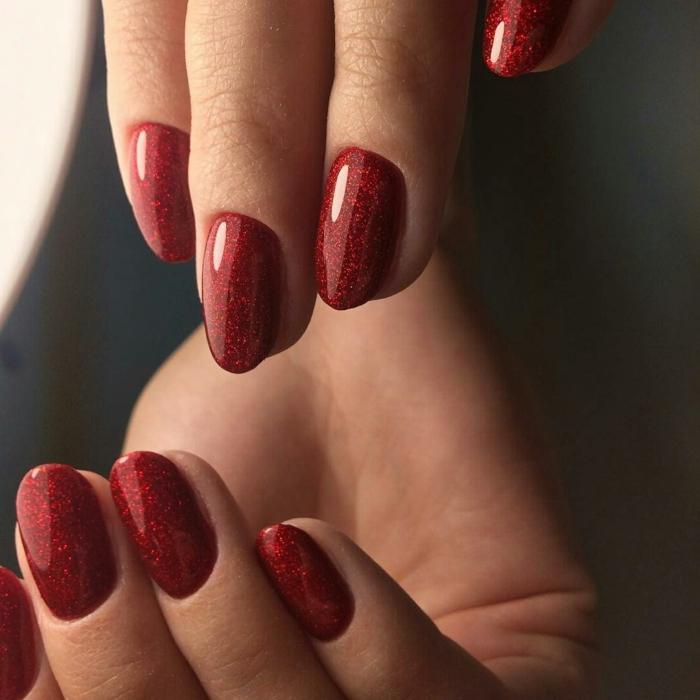 diseños de uñas de acrilico para Navidad, uñas pintadas en color rojo con partículas brillantes, uñas ovaladas
