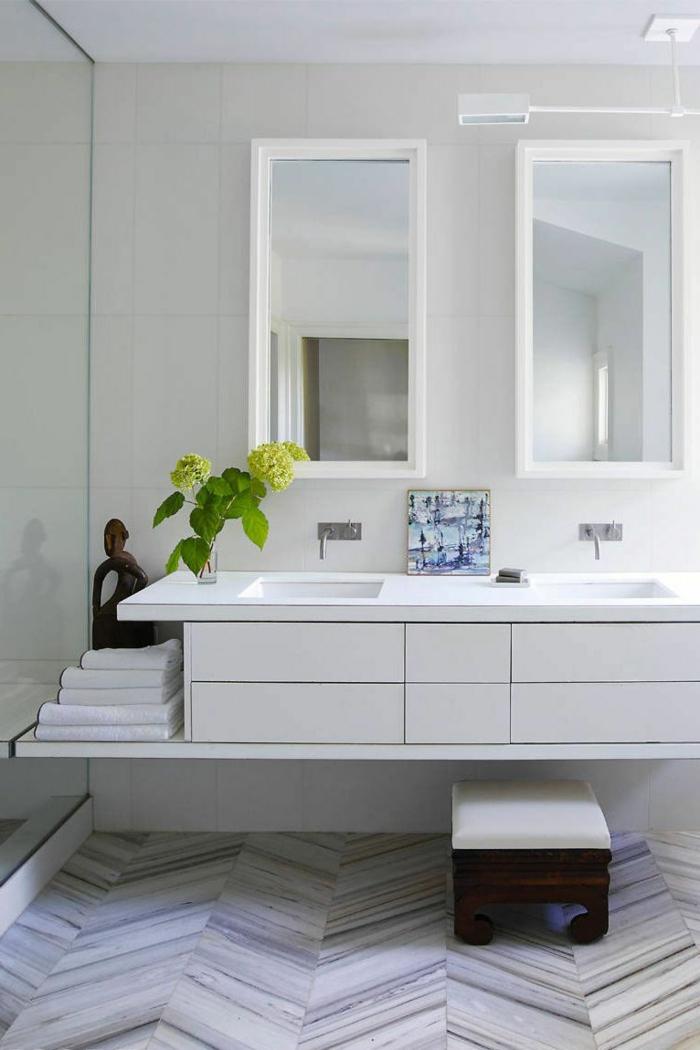 pequeño baño decorado en blanco y gris claro, azulejos de diseño, dos espejos modernos, pequeño taburete vintage