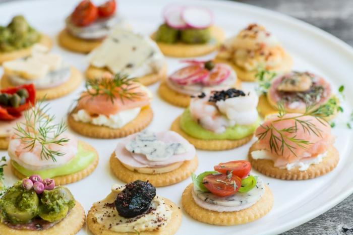 diversas propuestas de entrantes frios con crackers, queso, salmón ahumado, gambas, hummus casero