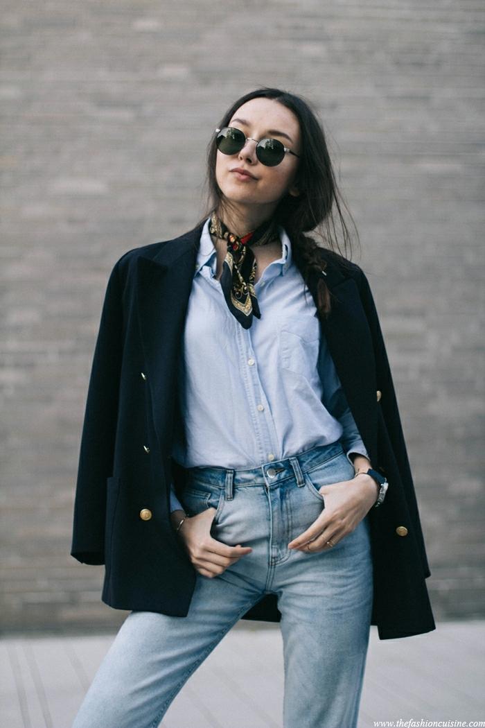 como ponerse un pañuelo en el cuello, atuendo clásico con un toque chic, vaqueros azules, camisa azul, abrigo negro con botones en dorado