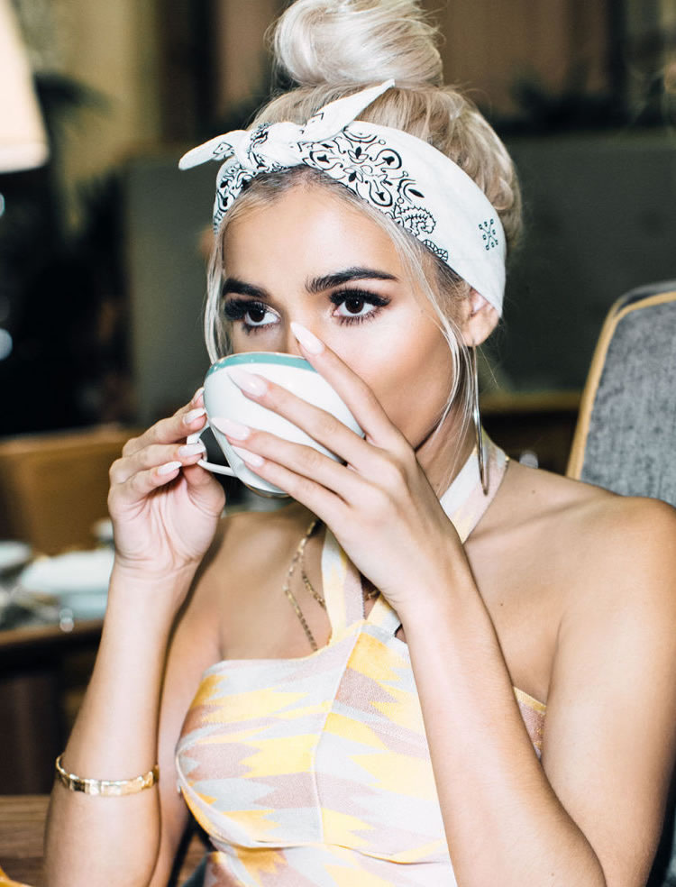 elegantes maneras de ponerse pañuelos para la cabeza, mujer con pelo recogido en moño alto, pañuelo blanco con ornamentos negros
