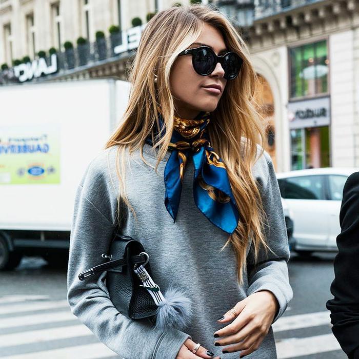 precioso outfit con un jersey deportivo en gris, bolso negro con pompon y pañuelo de seda en el cuello