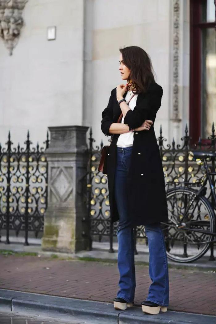 vaqueros azules, tacones altos en plataforma, blusa blanca, chaleco largo negro, pañuelo en el cuello
