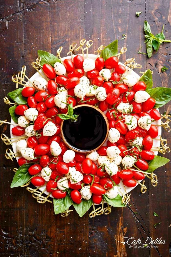 preciosas ideas de canapes navideños decorados, corona de navidad, ensalada caprese con queso mozzarella, tomates, albahaca