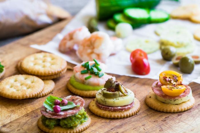 como hacer canapes para Navidad, diferentes propuestas de canapés con crackers, salsa de pesto casera, chorizo, queso