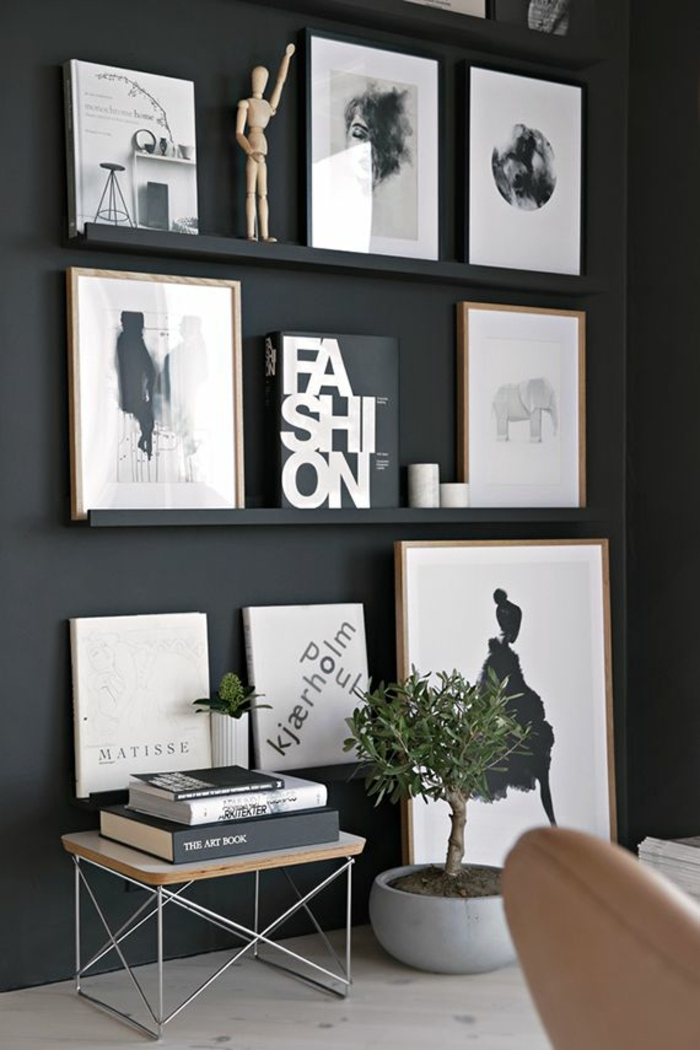 paredes pintadas originales, salón pintado en negro con muchos cuadros decorativos, muebles de diseño, plantas verdes