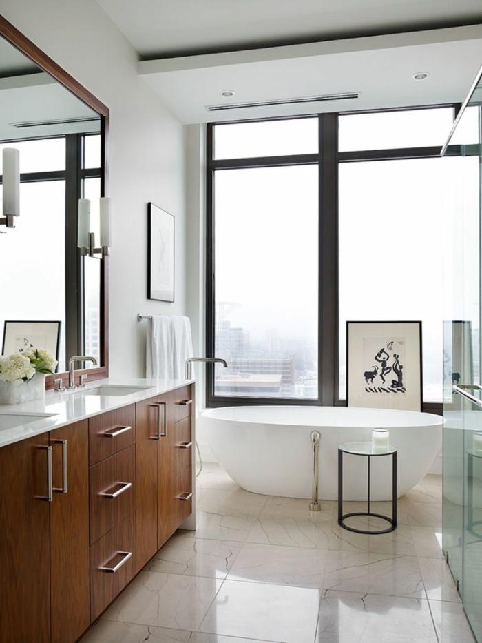 cuarto de baño de diseño decorado en colores claros, suelo con baldosas de mármol, bañera exenta oval y grandes ventanales