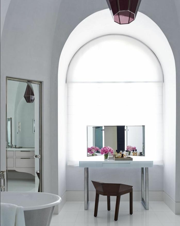 baño decorado en blanco inspirado en la estética vintage con grande espejo y interesante elemento arquitectónico
