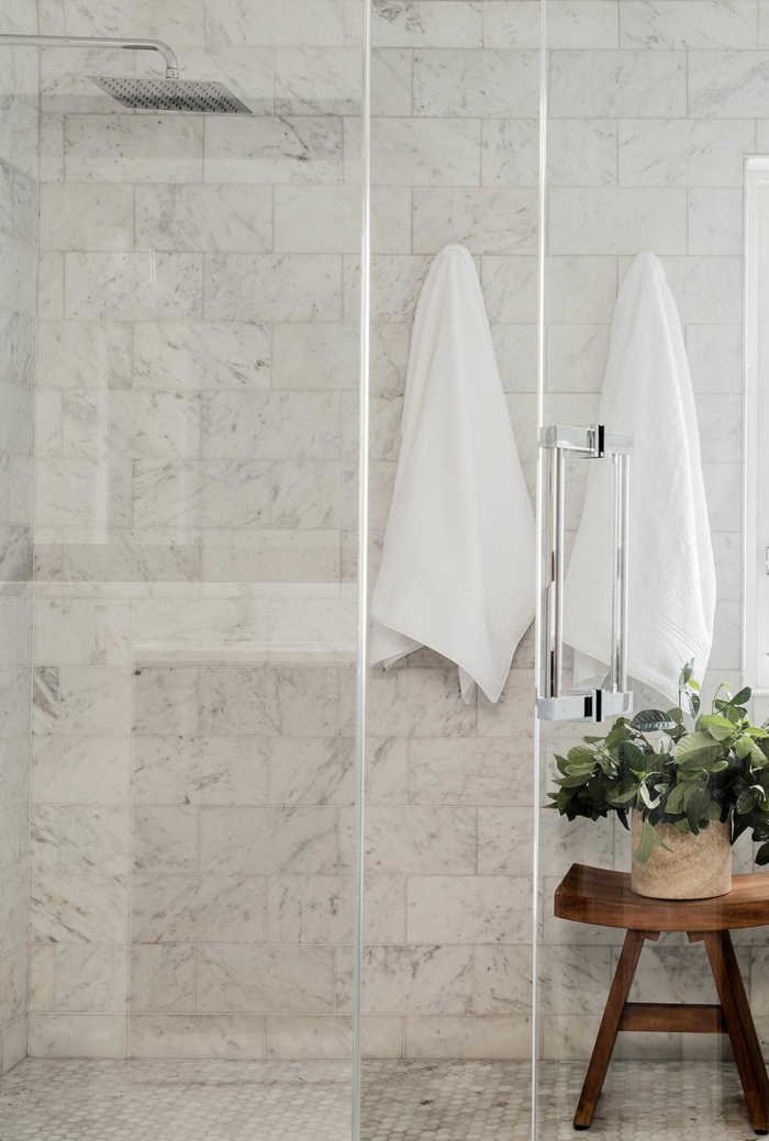 pequeño baño con azulejos de diseño de mármol, decoración plantas verdes, cabina de ducha