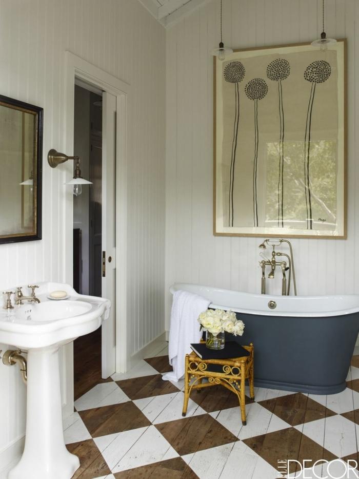 precioso baño decorado en colores claros estilo vintage, paredes en blanco, bañera de diseño y grande pintura en la pared