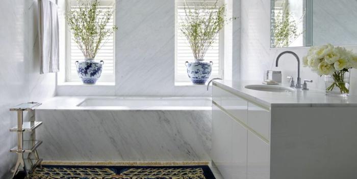 preciosa decoración cuarto de baño blanco, suelo con alfombra, bañera de mármol, decoración de flores