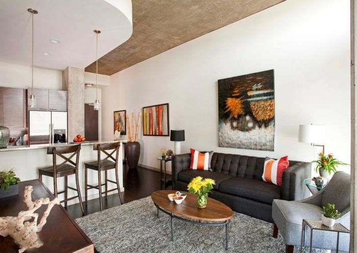 salón abierto al cocina, paredes pintadas en color blanco roto con muchas pinturas, muebles de diseño