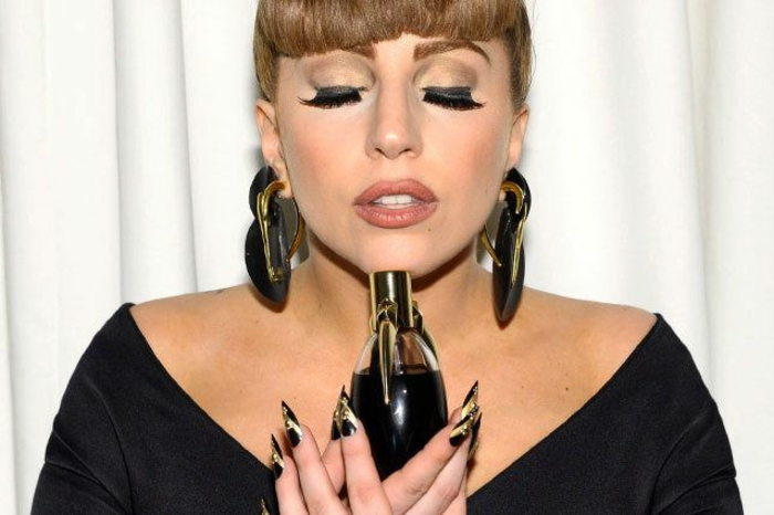 Lady Gaga con largas uñas con forma stilleto decoradas en negro y dorado, diseños de uñas modernos